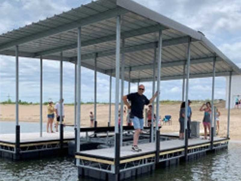 Man Standing on a floating dock with a canopy over it