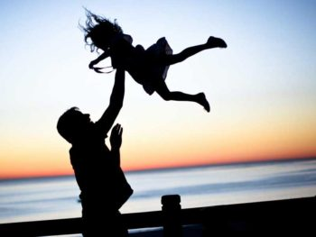 Silhouette of dad throwing daughter into air on a dock